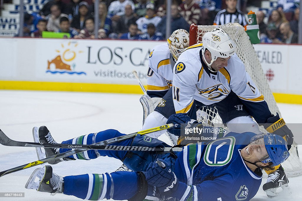 David Legwand of the Nashville Predators checks David Booth of the Vancouver Canucks to the ice during the second period on January 23 2014 at Rogers...