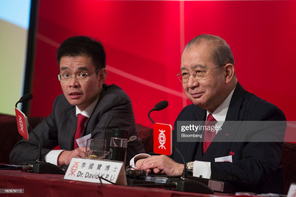 David Li, chairman and chief executive officer of Bank of East Asia Ltd. (BEA), right, reacts as Adrian Li, deputy chief executive officer, looks on during the company's annual results news conference in Hong Kong, China, on Tuesday, Feb. 26, 2013. Bank of East Asia, Hong Kong's largest family-run lender, said 2012 profit jumped 39 percent as trading income climbed, helping offset a decline in profit from the mainland China business. Photographer: Jerome Favre/Bloomberg via Getty Images