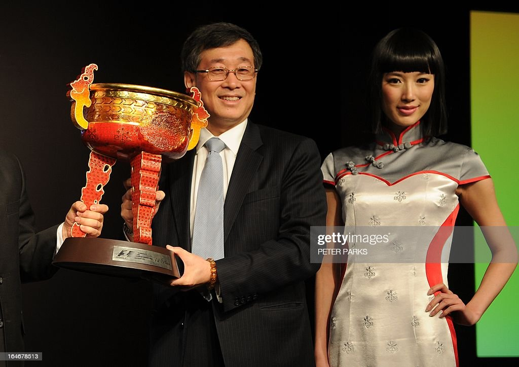 David Li (L) chairman and country head of UBS China holds the winner's trophy for the upcoming Formula One Chinese Grand Prix as a grid girl shows off a new outfit designed by celebrated local designer Simon Wang in Shanghai on March 26, 2013. The 10th Formula One Chinese Grand Prix will be held in Shanghai on April 14. AFP PHOTO/Peter PARKS