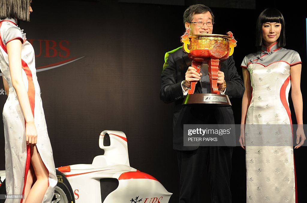 David Li (2nd-R) chairman and country head of UBS China holds the winner's trophy for the upcoming Formula One Chinese Grand Prix as grid girls show off new outfits designed by celebrated local designer Simon Wang in Shanghai on March 26, 2013. The 10th Formula One Chinese Grand Prix will be held in Shanghai on April 14. AFP PHOTO/Peter PARKS