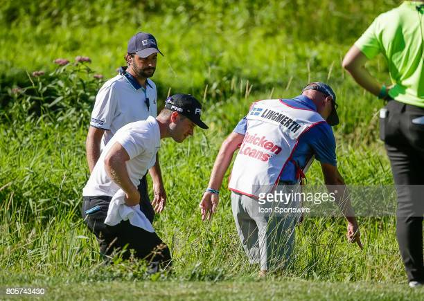 David Lingmerth and his caddie search for his ball in the muck on the left side of the 10th fairway during the third round of the Quicken Loans...