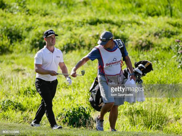 David Lingmerth hands his iron to his caddie after hitting out of the much along the left side of the 10th fairway during the third round of the...