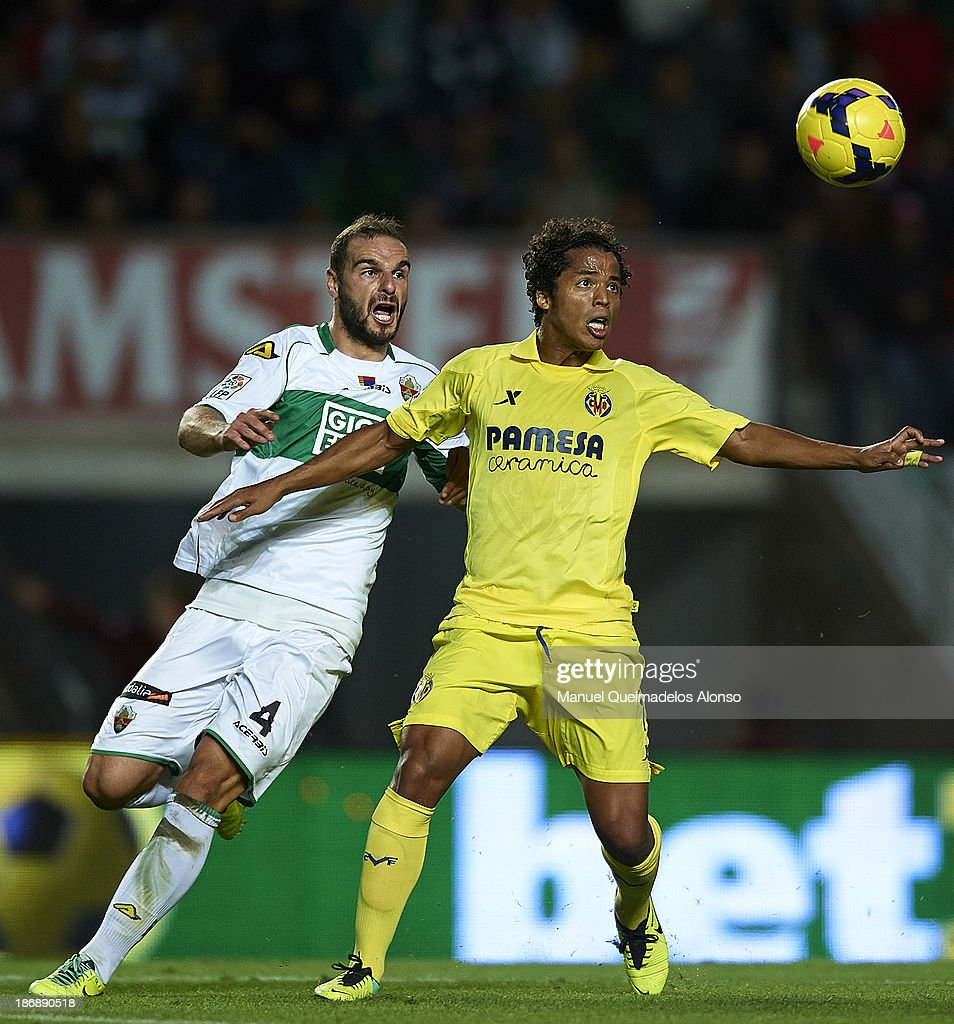 David Lomban (L) of Elche competes for the ball with Giovani Dos Santos of Villarreal during the La Liga match between Elche CF and Villarreal CF at Estadio Manuel Martinez Valero on November 4, 2013 in Elche, Spain.