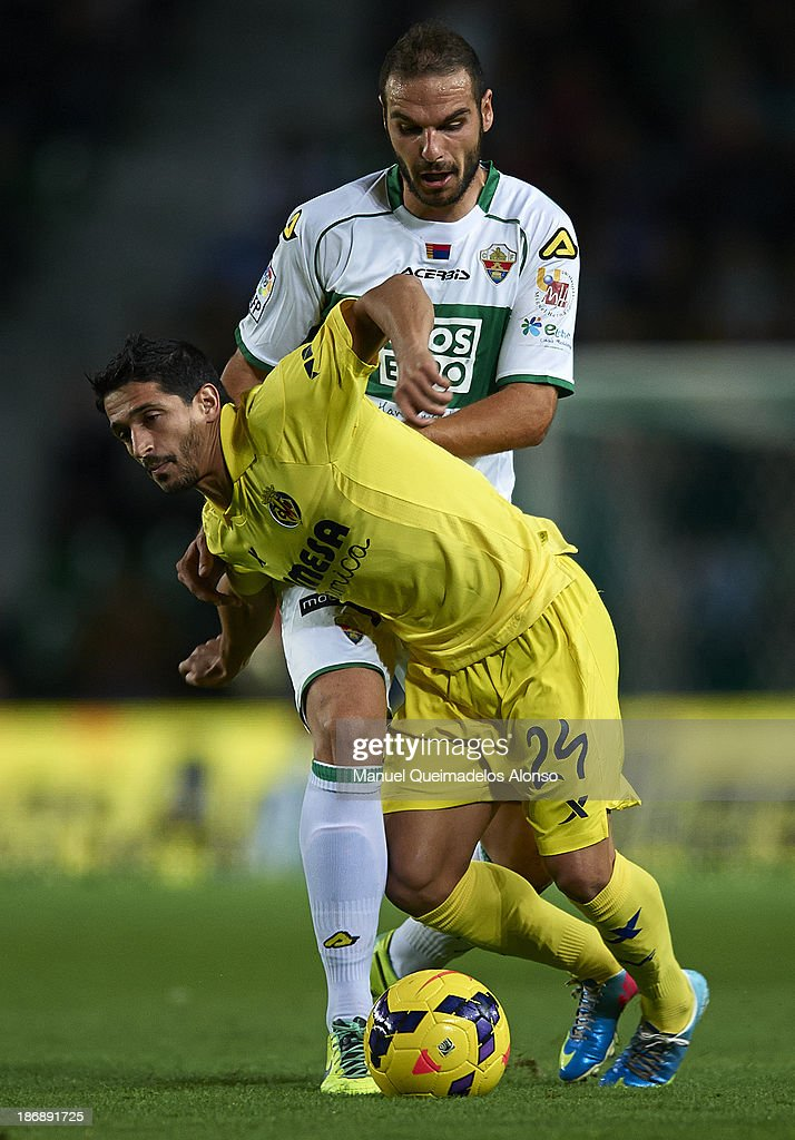 David Lomban (R) of Elche competes for the ball with Jonathan Pereira of Villarreal during the La Liga match between Elche CF and Villarreal CF at Estadio Manuel Martinez Valero on November 4, 2013 in Elche, Spain.