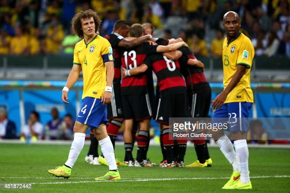 David Luiz and Maicon of Brazil look dejected after allowing Germany's fifth goal during the 2014 FIFA World Cup Brazil Semi Final match between...