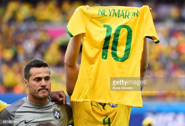 David Luiz of Brazil holds up a Neymar jersey as Julio Cesar looks on during the 2014 FIFA World Cup Brazil Semi Final match between Brazil and...
