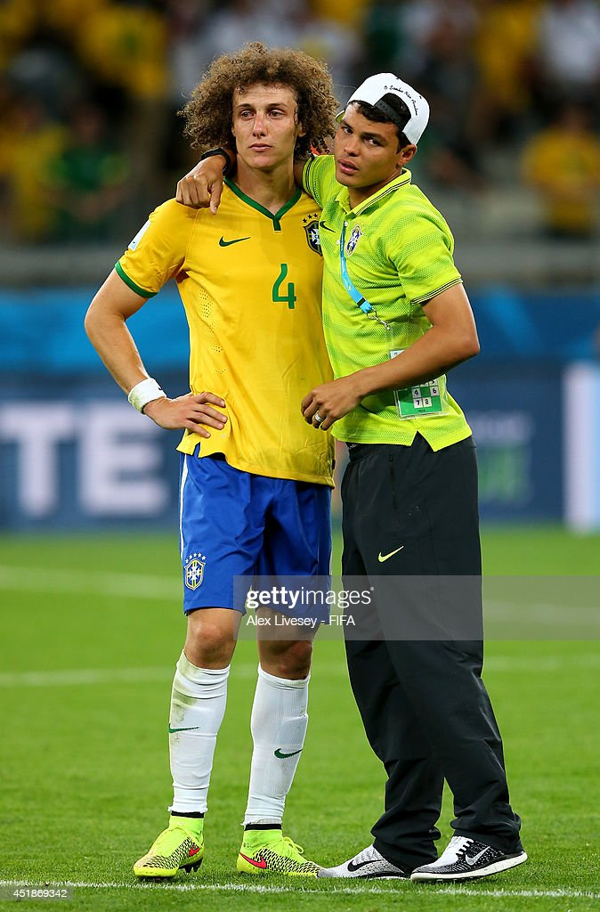 David Luiz (L) of Brazil is consoled by Thiago Silva after the 2014 FIFA World Cup Brazil Semi Final match between Brazil and Germany at Estadio Mineirao on July 8, 2014 in Belo Horizonte, Brazil.