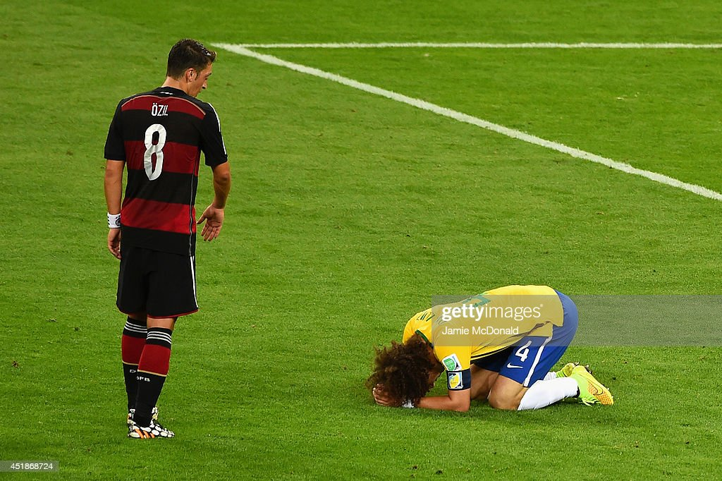 David Luiz of Brazil reacts after being defeated 71 by Germany as Mesut Oezil of Germany looks on during the 2014 FIFA World Cup Brazil Semi Final...