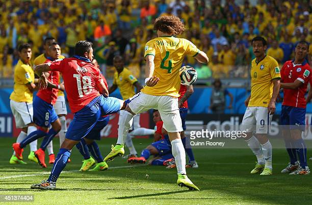 David Luiz of Brazil scores his team's first goal against Gonzalo Jara of Chile looks on during the 2014 FIFA World Cup Brazil round of 16 match...