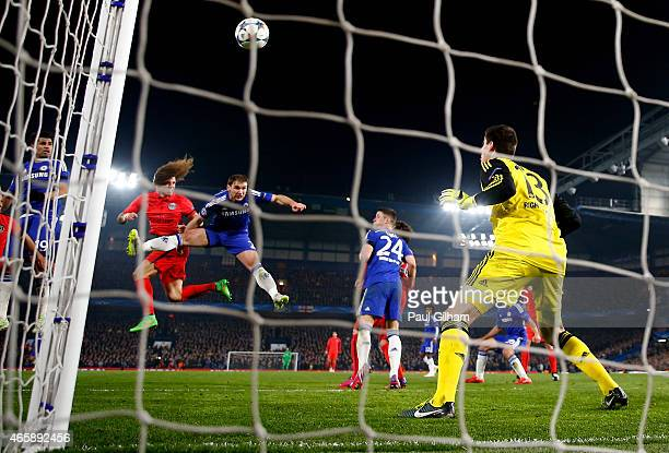 David Luiz of PSG rises above Branislav Ivanovic of Chelsea to score a gol past goalkeeper Thibaut Courtois of Chelsea to level the scores at 11...