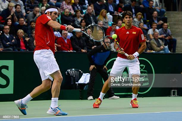 David Marrero of Spain plays a backhand in his Double match with Fernando Verdasco against Tommy Haas and Philipp Kohlschreiber of Germany on Day 2...
