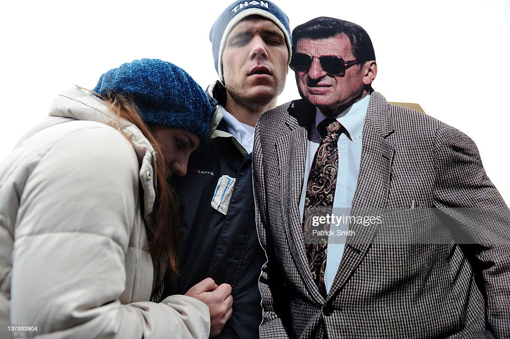 David Marselles (C) and Courtney O'Brien (L) share a moment next to a cardboard cutout of Joe Paterno, the former Penn State football coach, after hearing of Paterno's death outside of Beaver Stadium on January 22, 2012 in State College, Pennsylvania. Paterno, who was 85 years old, died due to complications from lung cancer.