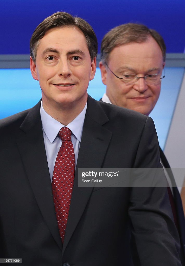 David McAllister (L), incumbent gubernatorial candidate of the German Christian Democrats (CDU), stands as Social Democrats (SPD) candidate Stephan Weil (L) walks by following a television news interview after initial poll results gave the CDU the highest number of votes following elections in Lower Saxony on January 20, 2013 in Hanover, Germany. Many see the Lower Saxony election as a bellwether for national elections scheduled for later this year.