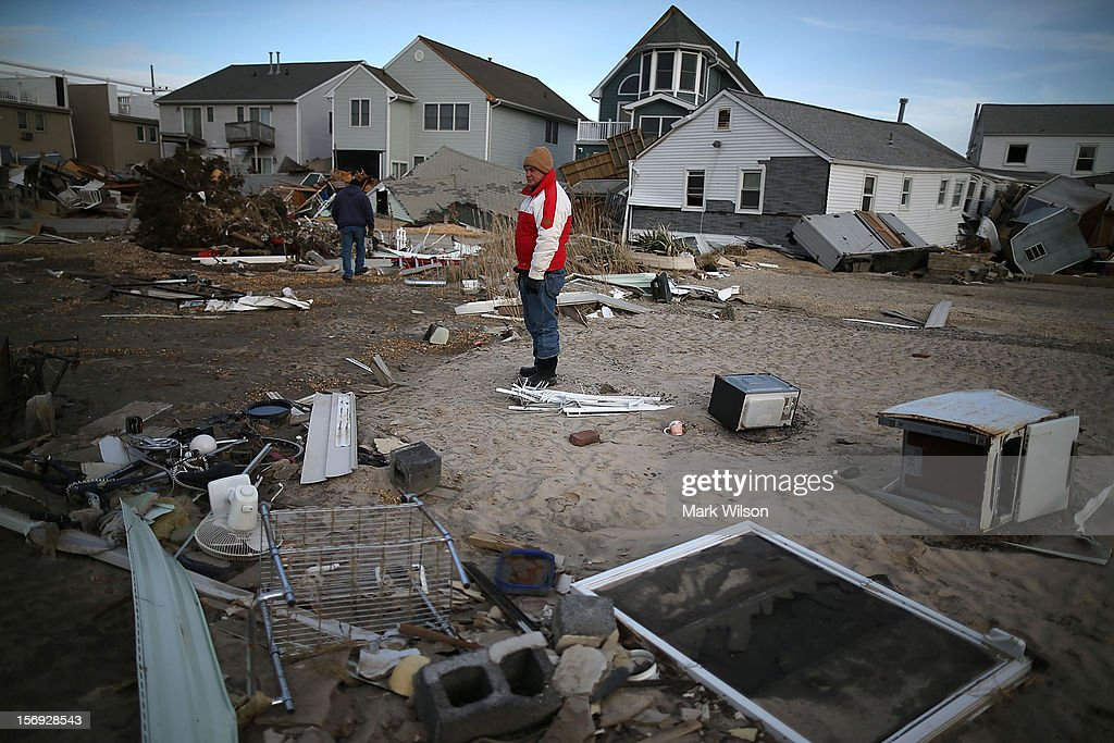 David Mccue (C), looks for pieces of his beach house that was completely demolished by Superstorm Sandy on November 25, 2012 in Ortley Beach, New Jersey. New Jersey Gov. Christie estimated that Superstorm Sandy cost New Jersey $29.4 billion in damage and economic losses.