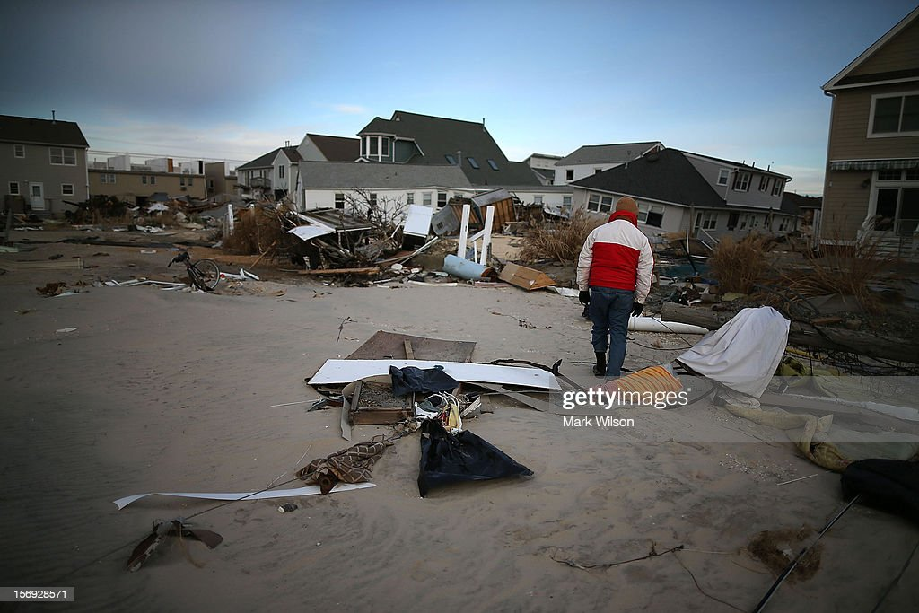 David Mccue looks for pieces of his beach house that was completely demolished by Superstorm Sandy on November 25, 2012 in Ortley Beach, New Jersey. New Jersey Gov. Christie estimated that Superstorm Sandy cost New Jersey $29.4 billion in damage and economic losses.