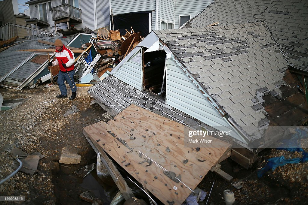 David Mccue stands near the roof to his beach house that was completely demolished by Superstorm Sandy on November 25, 2012 in Ortley Beach, New Jersey. New Jersey Gov. Christie estimated that Superstorm Sandy cost New Jersey $29.4 billion in damage and economic losses.