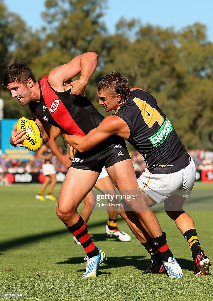 David Meyers of the Bombers is tackled by Dustin Martin of the Tigers during the round two AFL NAB Cup match between the Essendon Bombers and the Richmond Tigers at Wangaratta Showgrounds on March 2, 2013 in Wangaratta, Australia.