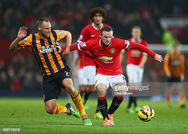 David Meyler of Hull City and Wayne Rooney of Manchester United battle for the ball during the Barclays Premier League match between Manchester...