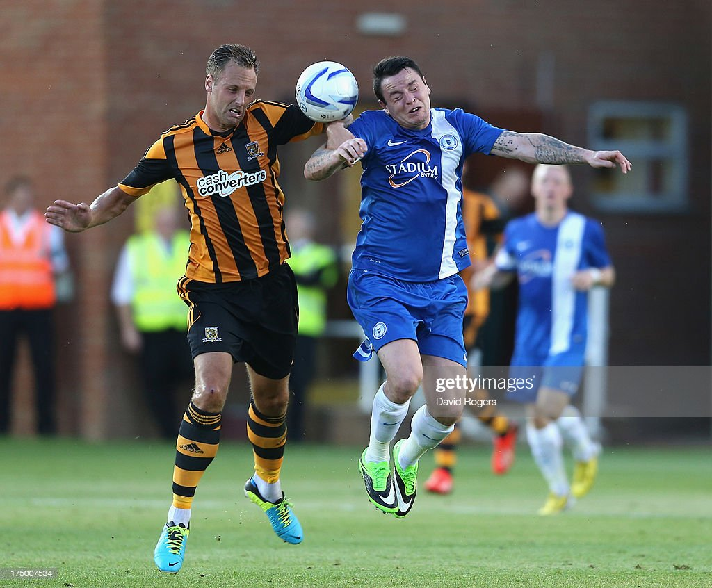 David Meyler (L) of Hull City challenges Lee Tomlin during the pre season friendly match between Peterborough United and Hull City at London Road Stadium on July 29, 2013 in Peterborough, England.