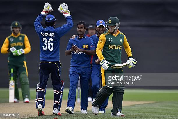 David Miller of South Africa walks from the field after being bowled out as Sri Lanka's Dinesh Chandimal and Nuwan Kulasekara celebrate during the...