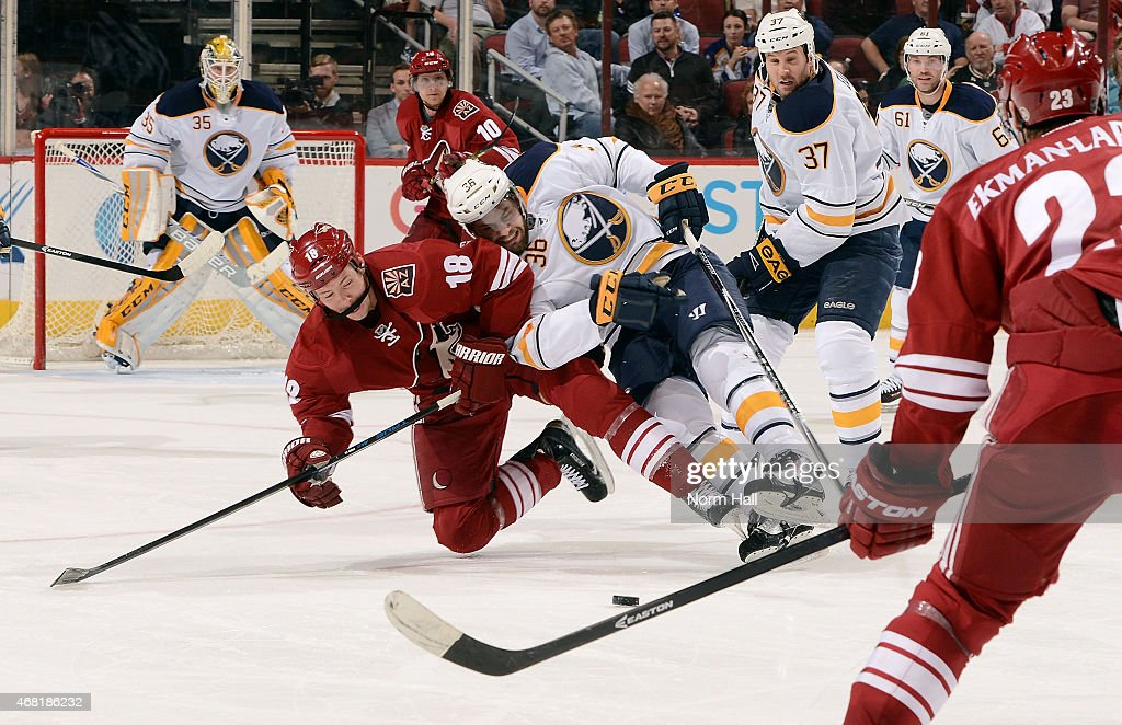 David Moss of the Arizona Coyotes is checked to the ice by Patrick Kaleta of the Buffalo Sabres during the third period at Gila River Arena on March...