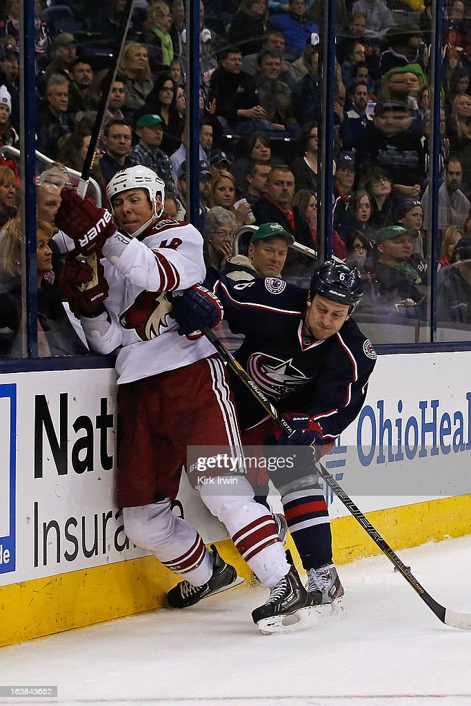 David Moss #18 of the Phoenix Coyotes is checked by <a gi-track='captionPersonalityLinkClicked' href=/galleries/search?phrase=Nikita+Nikitin&family=editorial&specificpeople=722107 ng-click='$event.stopPropagation()'>Nikita Nikitin</a> #6 of the Columbus Blue Jackets while chasing after a loose puck during the third period on March 16, 2013 at Nationwide Arena in Columbus, Ohio. Columbus defeated Phoenix 1-0 in a shootout.
