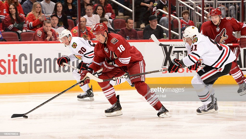 David Moss #18 of the Phoenix Coyotes skates the puck up ice past <a gi-track='captionPersonalityLinkClicked' href=/galleries/search?phrase=Marian+Hossa&family=editorial&specificpeople=202233 ng-click='$event.stopPropagation()'>Marian Hossa</a> #81 and Brandon Saad #20 of the Chicago Blackhawks during the third period at Jobing.com Arena on February 7, 2013 in Glendale, Arizona.