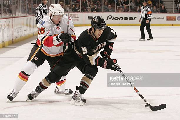 David Mossn of the Calgary Flames battles for the puck against Steve Montador of the Anaheim Ducks during the game on February 11 2009 at Honda...