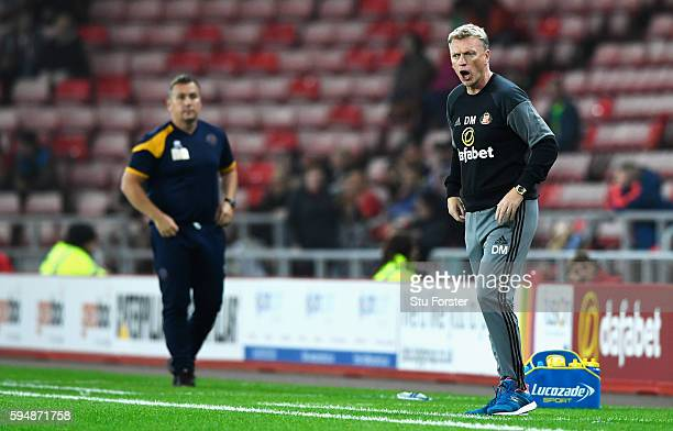 David Moyes Manager of Sunderland gives instructions with Micky Mellon Manager of Shrewsbury Town during the EFL Cup second round match between...