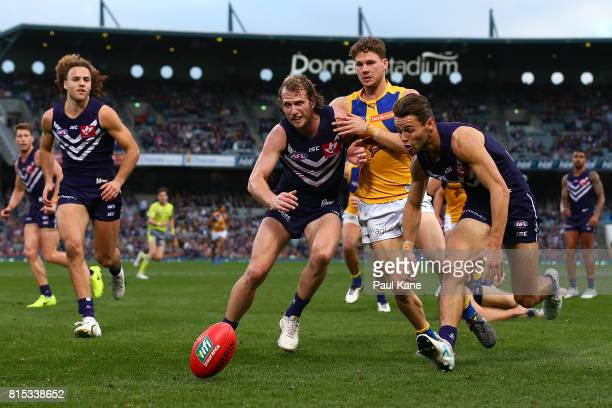 David Mundy and Lachie Weller of the Dockers contest for the ball against Jack Redden of the Eagles during the round 17 AFL match between the...