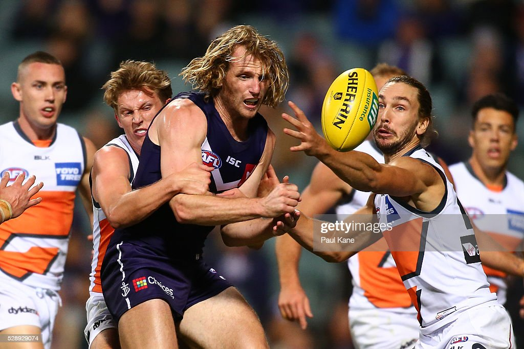 David Mundy of the Dockers gets his handball away while being tackled by Lachie Whitfield of the Giants during the round seven AFL match between the Fremantle Dockers and the Greater Western Sydney Giants at Domain Stadium on May 7, 2016 in Perth, Australia.