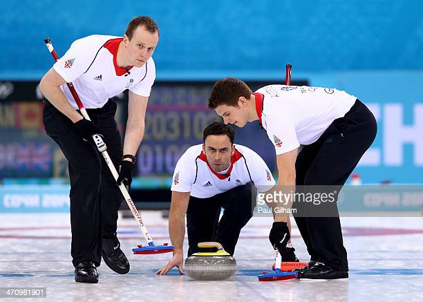 David Murdoch of Great Britain plays a stone as Michael Goodfellow and Scott Andrews during the Men's Gold Medal match between Canada and Great...