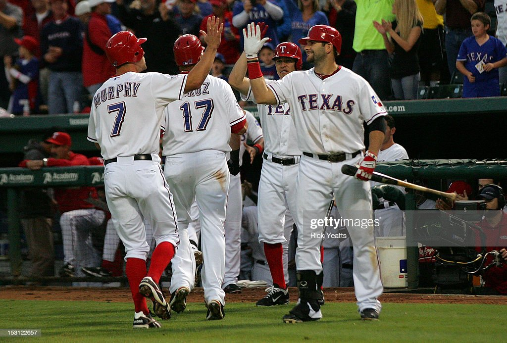 David Murphy #7 and <a gi-track='captionPersonalityLinkClicked' href=/galleries/search?phrase=Nelson+Cruz&family=editorial&specificpeople=235459 ng-click='$event.stopPropagation()'>Nelson Cruz</a> #17 celebrate with <a gi-track='captionPersonalityLinkClicked' href=/galleries/search?phrase=Mitch+Moreland&family=editorial&specificpeople=6824046 ng-click='$event.stopPropagation()'>Mitch Moreland</a> #18 of the Texas Rangers after scoring on Mike Napoli three run home run in game two of the double header against the Los Angeles Angels of Anaheim at Rangers Ballpark in Arlington on September 30, 2012 in Arlington, Texas.