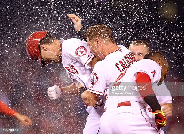David Murphy of the Los Angeles Angels of Anaheim is mobbed by teammates including Kole Calhoun and sprayed with water after his walk off RBI single...