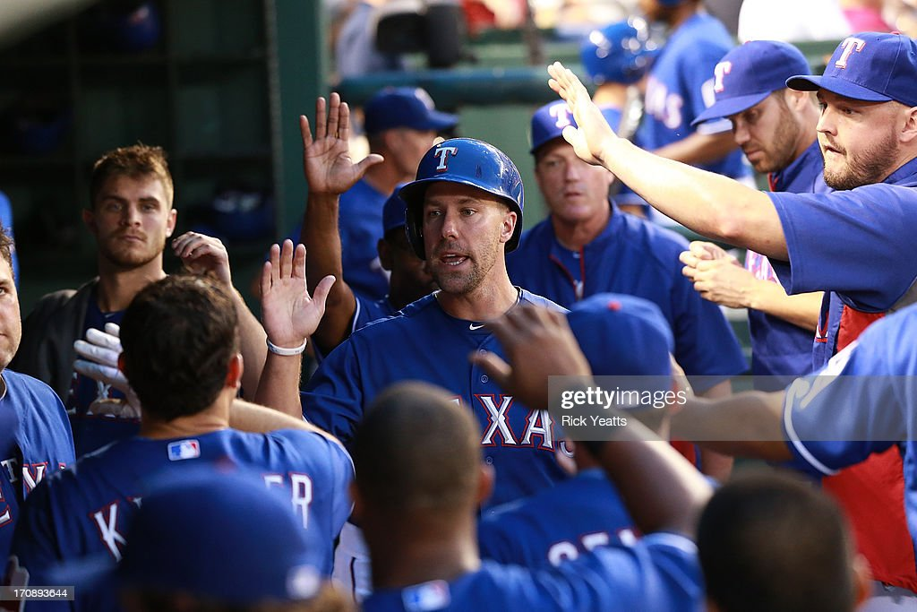David Murphy #7 of the Texas Rangers is congratulated by his team mates for scoring in the fifth inning against the Oakland Athletics on a sacrifice fly hit by Ian Kinsler at Rangers Ballpark in Arlington on June 19, 2013 in Arlington, Texas.