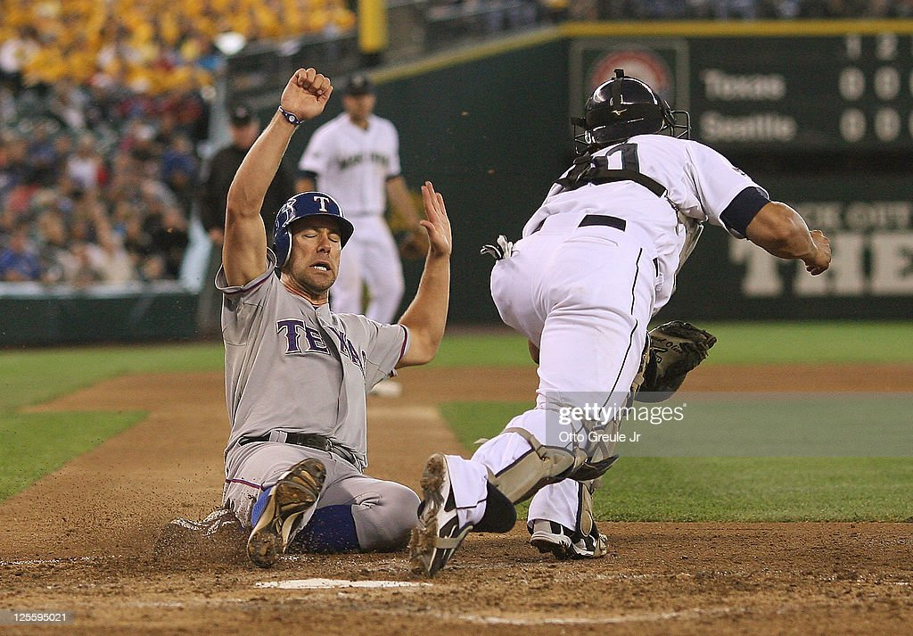 David Murphy #7 of the Texas Rangers is forced out at home as catcher <a gi-track='captionPersonalityLinkClicked' href=/galleries/search?phrase=Miguel+Olivo&family=editorial&specificpeople=209185 ng-click='$event.stopPropagation()'>Miguel Olivo</a> #30 of the Seattle Mariners takes the throw in the seventh inning at Safeco Field on September 18, 2011 in Seattle, Washington. The Rangers defeated the Mariners 3-0.