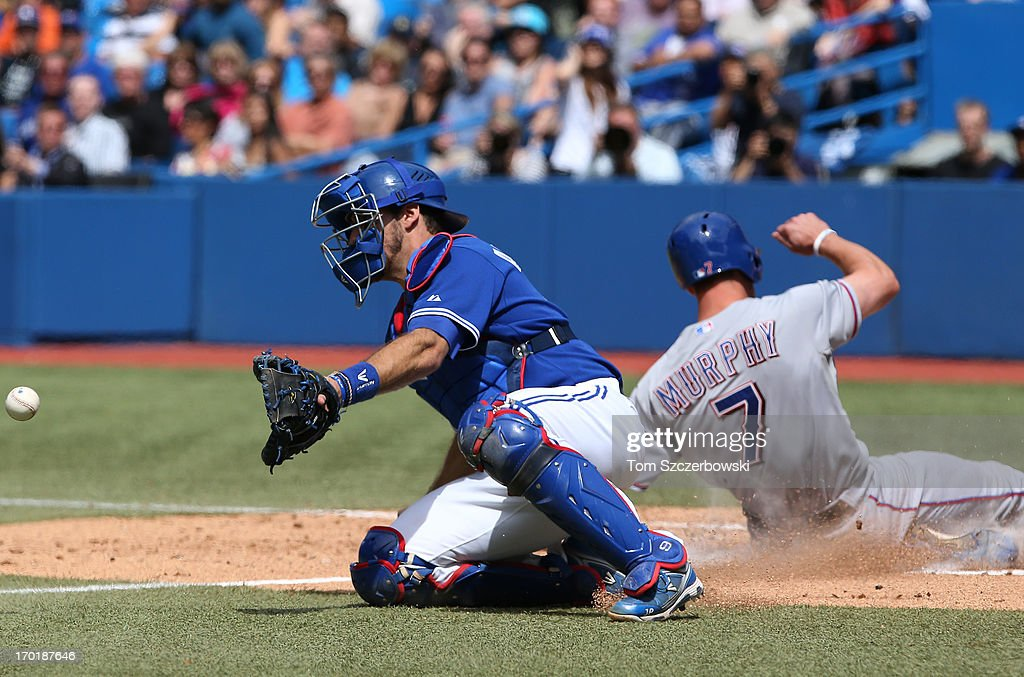 David Murphy #7 of the Texas Rangers slides across home plate to score the tying run in the ninth inning during MLB game action as J.P. Arencibia #9 of the Toronto Blue Jays waits for the throw on June 8, 2013 at Rogers Centre in Toronto, Ontario, Canada.