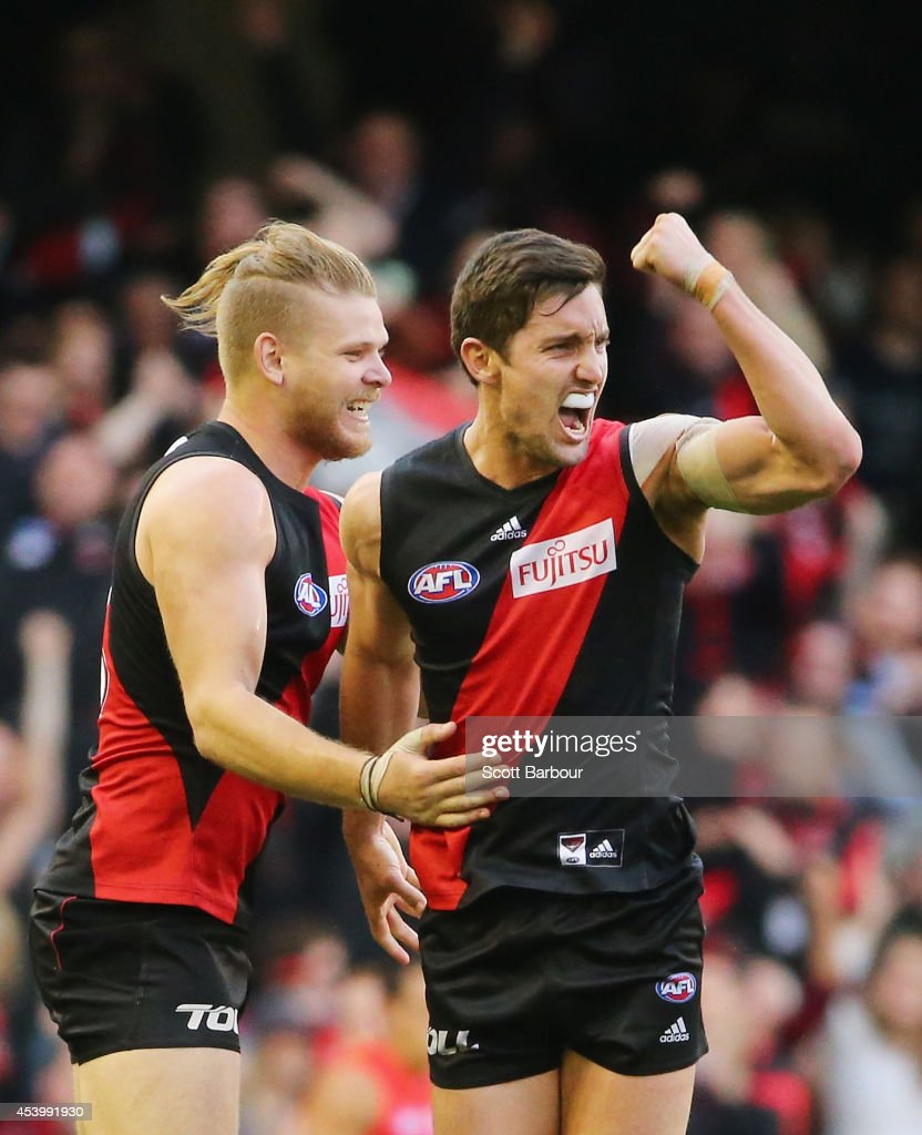 David Myers of the Bombers is congratulated by Michael Hurley after kicking a goal during the round 22 AFL match between the Essendon Bombers and the...