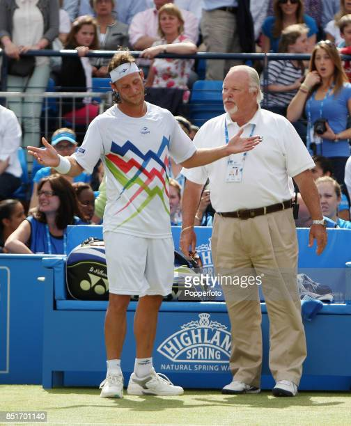 David Nalbandian of Argentina is disqualified by tournament referee Jimmy Moore after injuring line judge Andrew McDougall's leg during his men's...