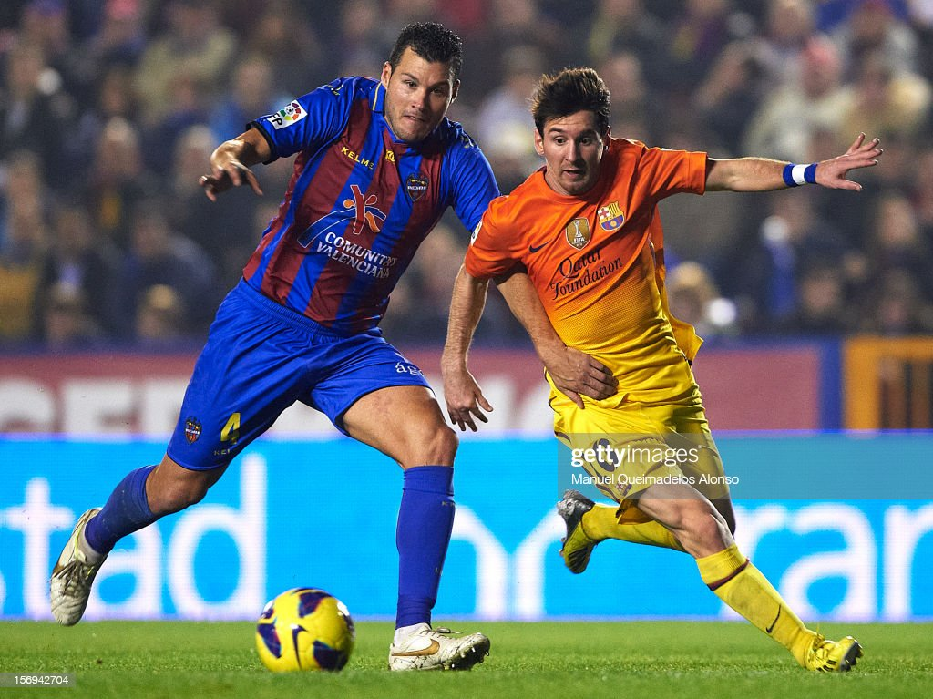 David Navarro (L) of Levante competes for the ball with <a gi-track='captionPersonalityLinkClicked' href=/galleries/search?phrase=Lionel+Messi&family=editorial&specificpeople=453305 ng-click='$event.stopPropagation()'>Lionel Messi</a> of Barcelona during the la Liga match between Levante UD and FC Barcelona at Ciutat de Valencia on November 25, 2012 in Valencia, Spain.