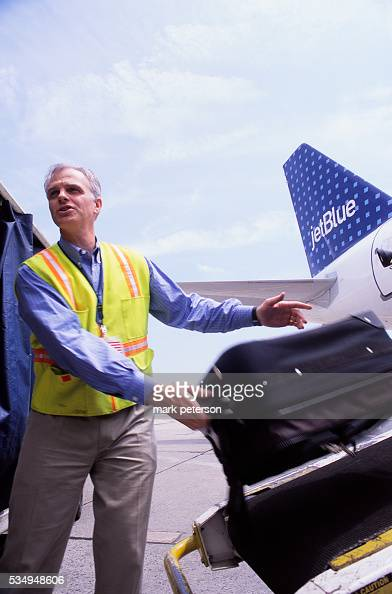 David Neeleman CEO of JetBlue Airways helps employees load luggage onto a plane at John F Kennedy International Airport JetBlue Airways was launched...