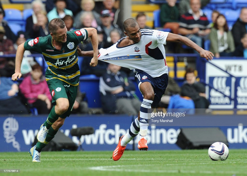 David Ngog of Bolton Wanderers is pulled back by his shirt by Clint Hill of Queens Park Rangers during the Sky Bet Championship match between Bolton Wanderers and Queens Park Rangers at Reebok Stadium on August 24, 2013 in Bolton, England,