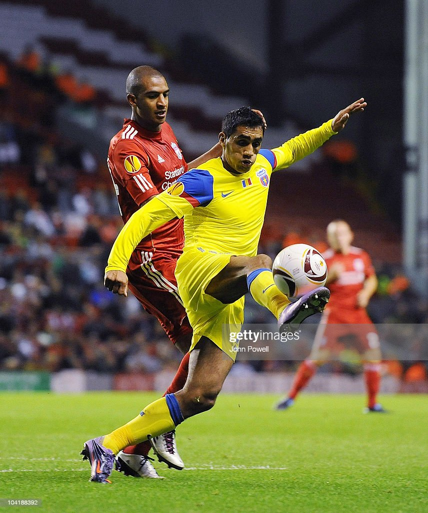 David Ngog of Liverpool tussles with Banel Nicolita of Steau Bucharest during the first leg UEFA Europa League match between Liverpool and Steau Bucharest on September 16, 2010 in Liverpool, England.