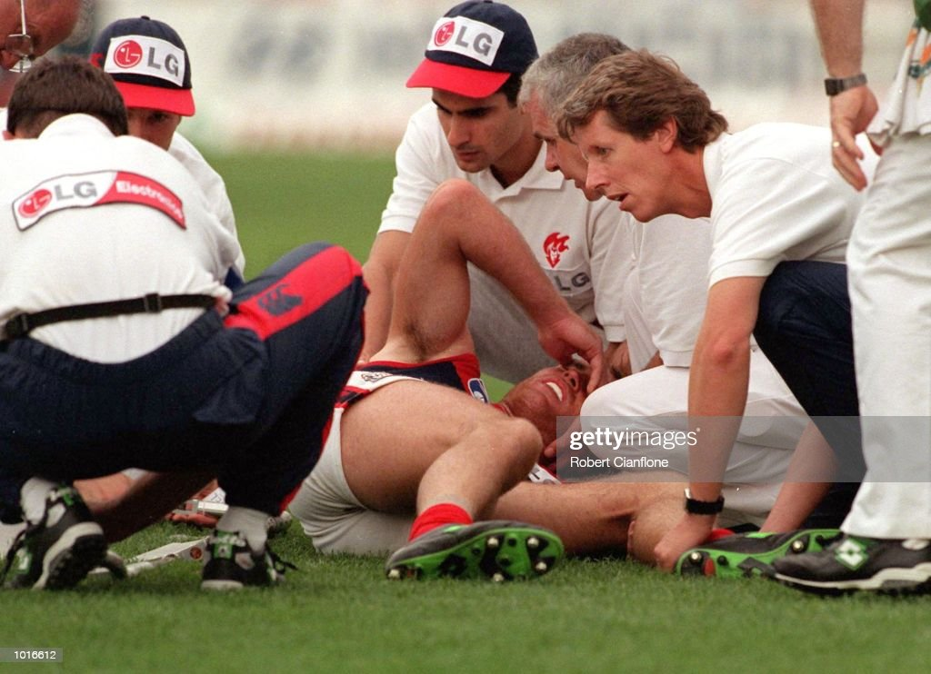 David Nietz of Melbourne is assisted by the trainers after sustaining an injury, in the match between Carlton and Melbourne, during round four of the AFL season, played at the Melbourne Cricket Ground, Melbourne, Australia. Mandatory Credit: RobertCianflone/ALLSPORT