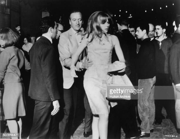 David Niven and Francoise Dorleac move in a crowd in a scene from the MGM movie 'Where the Spies Are' circa 1965