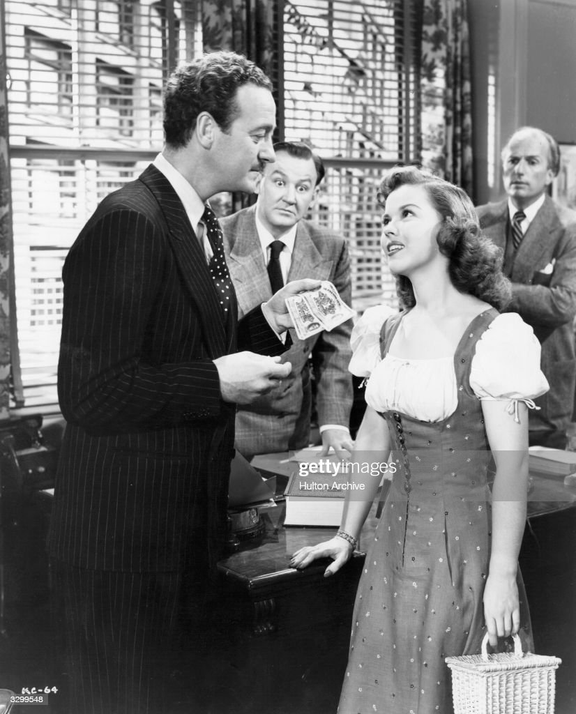 <a gi-track='captionPersonalityLinkClicked' href=/galleries/search?phrase=David+Niven&family=editorial&specificpeople=123835 ng-click='$event.stopPropagation()'>David Niven</a> (1909 - 1983) the British leading man offers money to <a gi-track='captionPersonalityLinkClicked' href=/galleries/search?phrase=Shirley+Temple&family=editorial&specificpeople=69996 ng-click='$event.stopPropagation()'>Shirley Temple</a>, the child star prodigy in 'A Kiss For Corliss', about a teenager who has a crush on a middle aged roue. The film was directed by Richard Wallace for United Artists.
