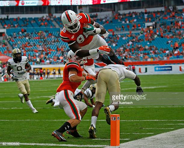 David Njoku of the Miami Hurricanes dives over Terrish Webb of the Pittsburgh Panthers to score a first quarter touchdown on November 5 2016 at Hard...