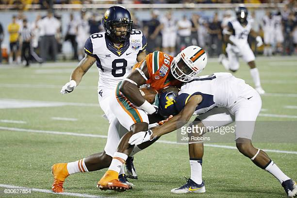 David Njoku of the Miami Hurricanes gets tackled after a reception against the West Virginia Mountaineers in the first half of the Russell Athletic...
