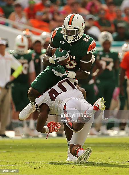 David Njoku of the Miami Hurricanes is tackled by Deon Clarke of the Virginia Tech Hokies during a game at Sun Life Stadium on October 17 2015 in...