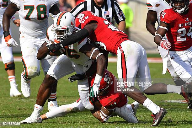 David Njoku of the Miami Hurricanes is tackled by Jack Tocho and Josh Jones of the North Carolina State Wolfpack at CarterFinley Stadium on November...
